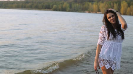 милый : girl walking on the river at sunset, girl smiling