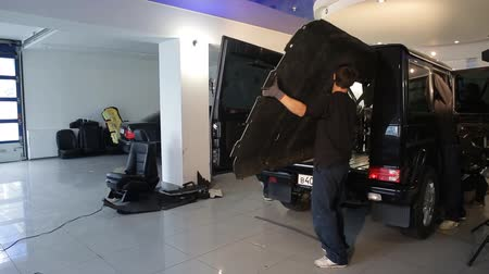 unscrewing : man dismantle the machine for sound insulation,soundproofing Stock Footage