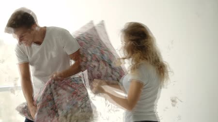 almofada : Young couple fighting pillows in the photostudio Vídeos