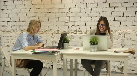 desteklemek : Two smilling businesswomen working on laptop at office and smilling Stok Video