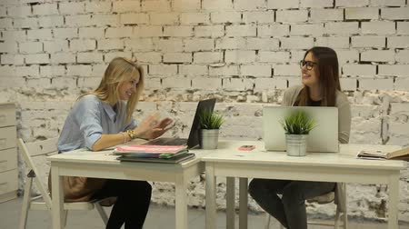 career success : Two smilling businesswomen working on laptop at office and smilling Stock Footage
