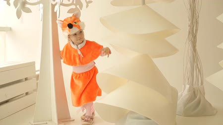 kostüm : Little child girl dressed in fox suit near Christmas tree. The concept of New Year and holiday Stok Video