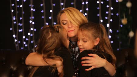 мама : happy mother hugging twin daughters in New year Стоковые видеозаписи
