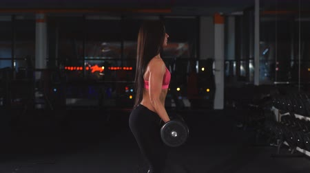 сильный : the girl does exercises on a biceps with dumbbells Стоковые видеозаписи