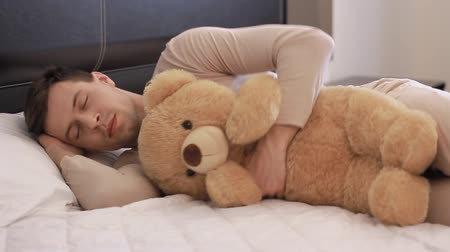 teddy bear : Guy is slapen met teddy bear  Stockvideo