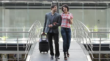 kufr : A man and a woman are going over the bridge with suitcase (PAL)