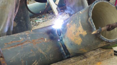 oxyacetylene : Welder uses arc welding pipe metal on site in outdoor.