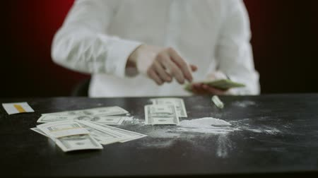 snorting : folding money on the table wiith cocaine