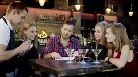három ember : Happy young people sitting in the bar reading menu card and giving orders to the male waiter