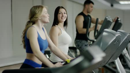trabalhar fora : smiling Pretty women walking on treadmill talking Vídeos
