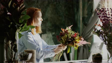florista : ginger florist arranging bunch of flowers at green background Stock Footage