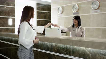 vendégszeretet : young woman gets a key in hotel for room