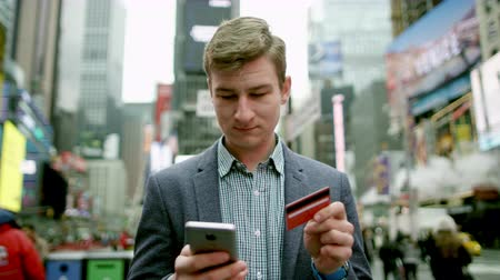 wzrok : Young man buying something over the Internet on Times Square