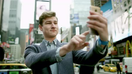 рекламный : Young man taking a picture of himself on Times Square on a smartphone camera