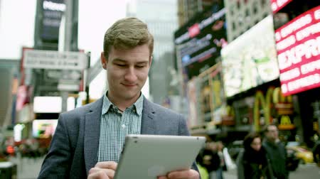 рекламный : Young man with a tablet pc on Times Square Стоковые видеозаписи