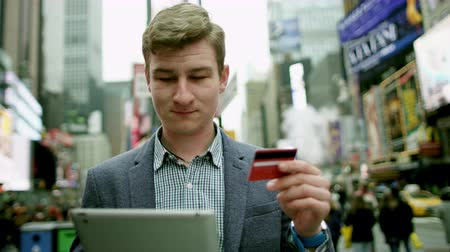 рекламный : Young man shopping online on Times Square by using his tablet pc and a card Стоковые видеозаписи