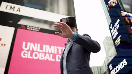 рекламный : Young man with virtual reality glasses on Times Square
