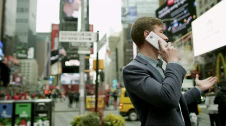 wzrok : Attractive young man talking over his smartphone on Times Square Wideo