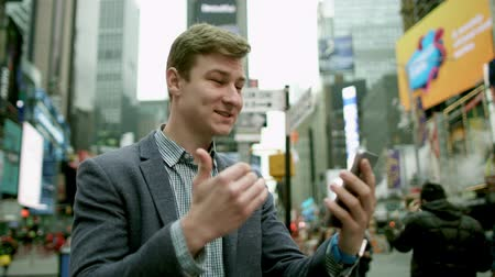 wzrok : Cheerful young man having a video chat on Times Square by using his smartphopne