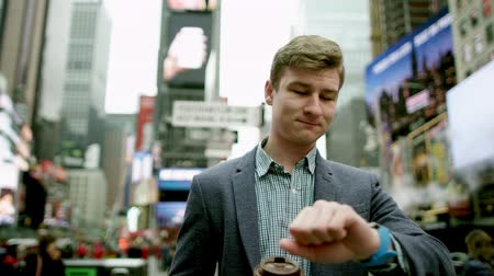 wzrok : Young man on Times Square with a cup of coffee looking on his watch and walking away