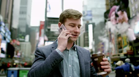 рекламный : Young man drinking tea and talking over his smartphone on Times Square