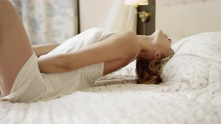 Young attractive woman posing on bed in white sleepwear shirt