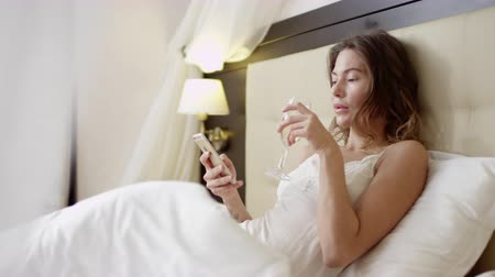 Young beautiful woman checking newsfeed on her smartphone while drinking champagne in bed Dostupné videozáznamy
