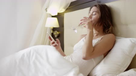 Young beautiful woman dressed in sexy outfit texting on her smartphone while drinking champagne in bed