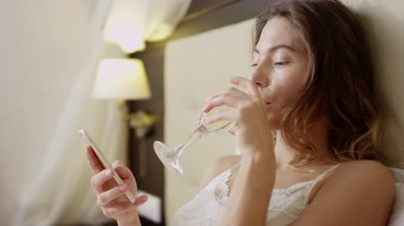 Beautiful woman surfing the Internet on a smartphone while drinking champagne in bed Dostupné videozáznamy