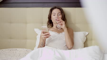 Young woman watch news on a smartphone while drinking champagne in bed