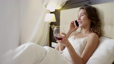 linen : Beautiful woman drinks wine and talks over cellphone on bed Stock Footage