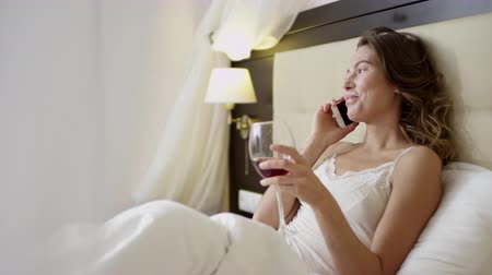Model drinks wine and talks over smartphone on bed