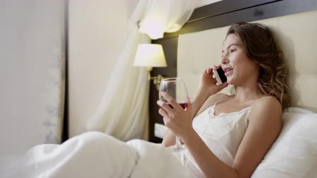 Woman drinks wine and talks over mobile phone on bed Dostupné videozáznamy