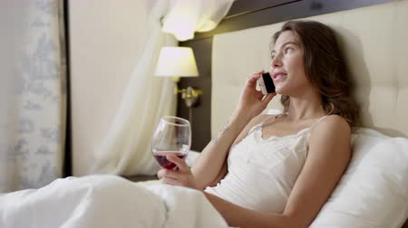 Young woman having a phone talk over smartphone while drinking wine on bed