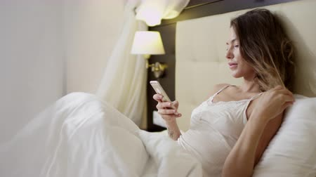 Young beautiful woman lying on bed and checking social networks on a smartphone