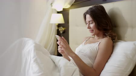 yalan : Young sexy dressed woman lying on bed and texting over her smartphone