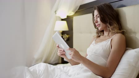 Young beautiful woman using digital tablet lying in bed