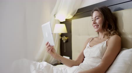 Young woman having a video chat on her tablet pc while lying on bed