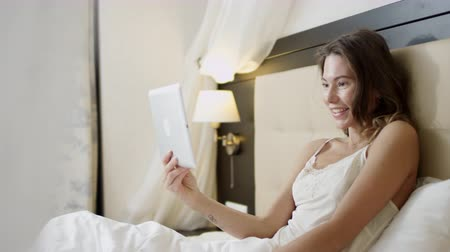 Cheerful woman lying in bed and having a video chat on her digital tablet Dostupné videozáznamy