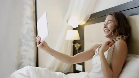 Smiling woman lying in bed is having a video chat over her tablet pc Dostupné videozáznamy