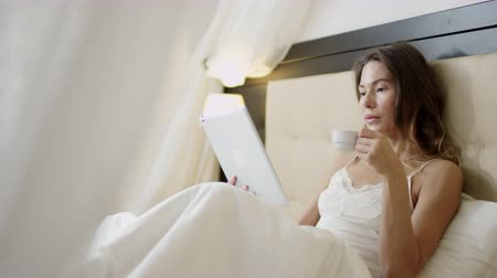 Woman using tablet pc in bed while drinking coffee