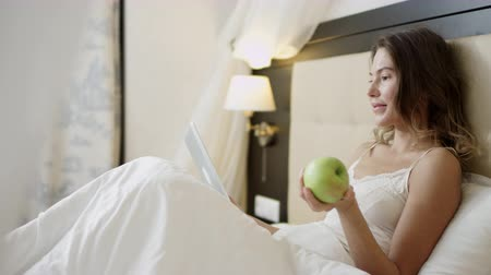 Woman lies in bed while holding apple while using a tablet pc