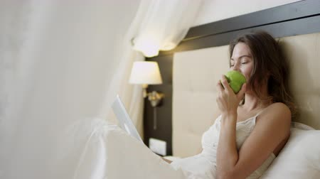 Woman lying on bed with a tablet pc is sniffing a green apple in her hand Dostupné videozáznamy