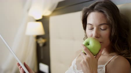 Woman watching movie on her tablet pc and sniffing an apple while lying on bed