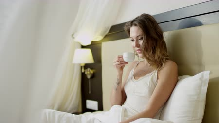 Young beautiful woman using laptop while drinking coffee in bed