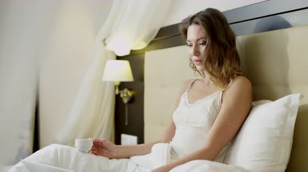 Gorgeous woman reading news on her laptop while drinking coffee on bed