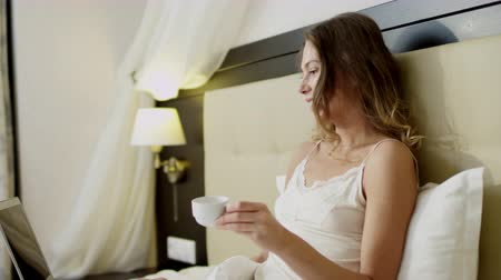 Young woman lies in bed, drinks coffee and having a video chat over her laptop Dostupné videozáznamy