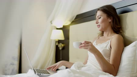 Young woman doing video translation on her laptop while drinking coffee in bed