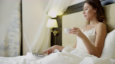 Gorgeous woman doing video translation on her laptop while drinking coffee in bed
