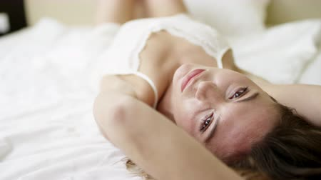 mentiras : Sleepy woman lies on bed on her back and posing Vídeos